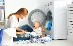 Mom & Baby Folding Laundry in front of the Washing Machine