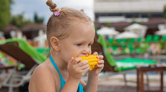 Little girl eating real food corn